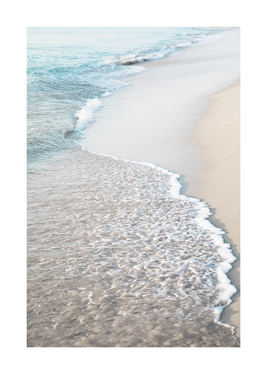 – Photograph of a beach with light sand and waves coming onto the beach