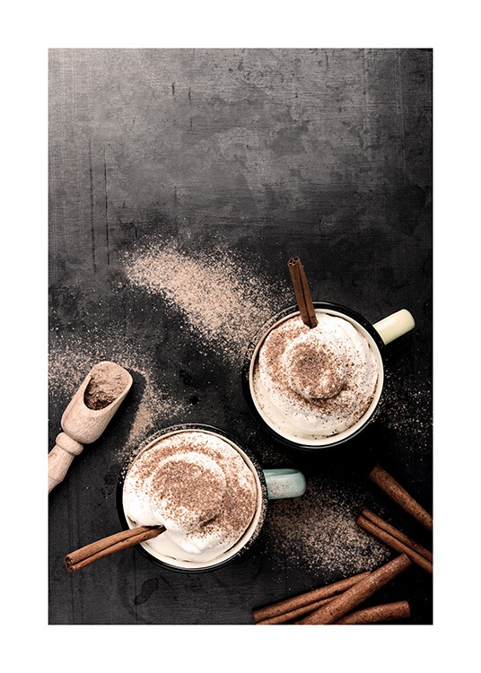 – Photograph of two cups from above, with cinnamon sticks and whipped cream in them