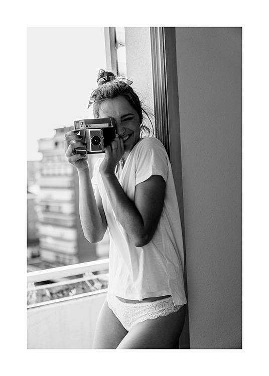 Black and white photograph of woman smiling while holding a camera and wearing white t-shirt