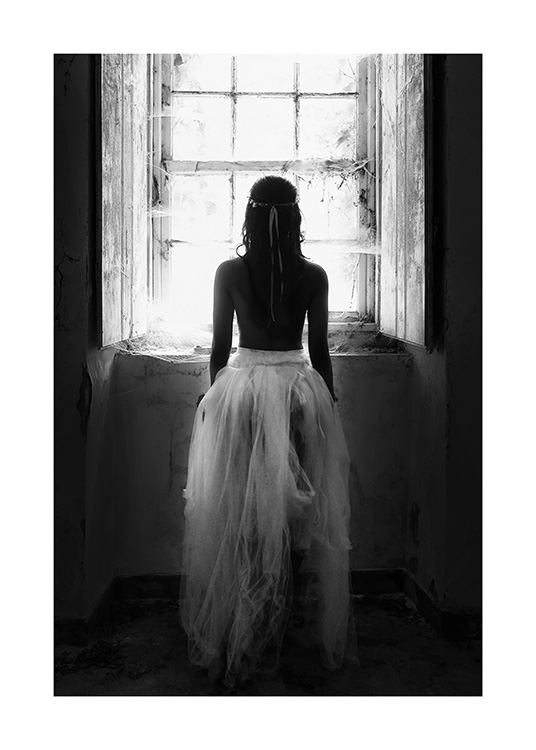 Black and white photograph of woman standing in front of window in tulle skirt