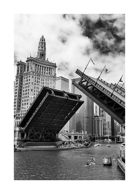 - Black and white photograph of Chicago Bridge being opened, with boats on the river and buildings in the background