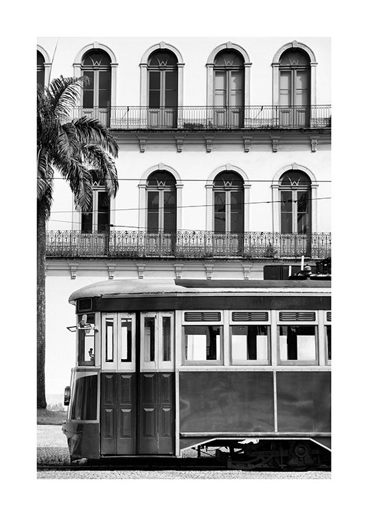 - Black and white photograph with a building with balconies behind a vintage tram, with a palm tree on the side