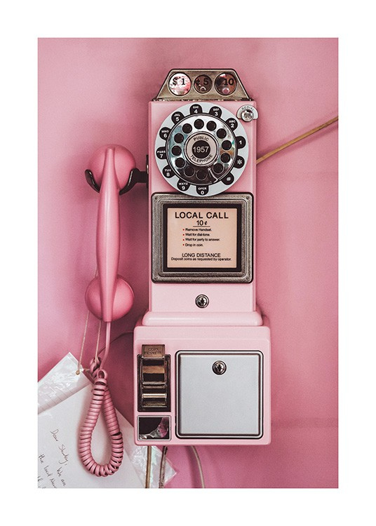 - Photograph of a pink pay phone with a retro style, on a pink background