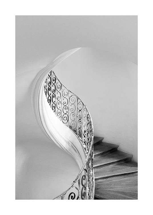 - Black and white photograph of a tulip staircase with a black banister, surrounded by light walls