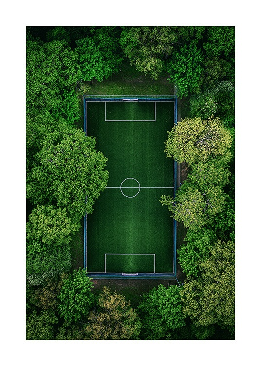 - Photograph from above of thick green trees that surrounds a green football pitch
