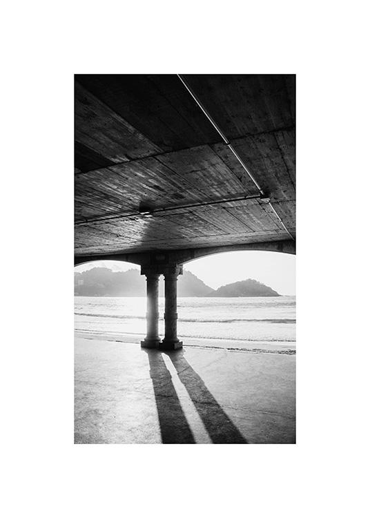 – Black and white photograph of a pier with two pillars with a beach and mountains in the background