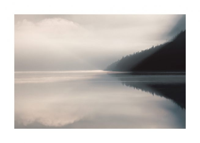 – Photograph of a foggy lake with still water and a forest in the background