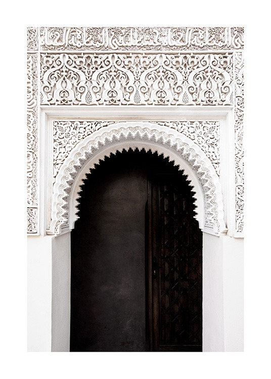 - Photograph of a black door and a white arch with handcrafted details and patterns
