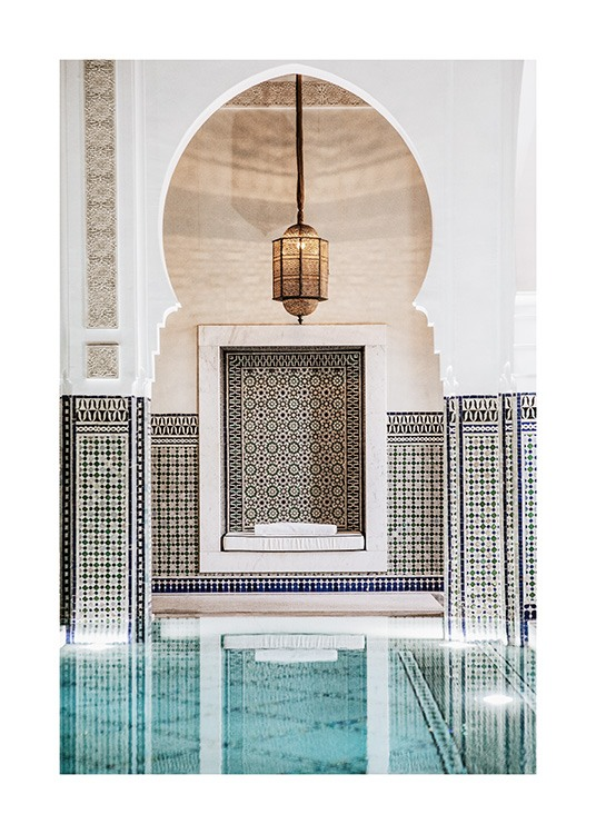 - Photograph of a gold lamp and a white arch with blue mosaic patterns behind a pool