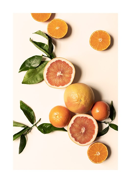 – Photograph of clementines, oranges and green leaves laying on a light yellow background