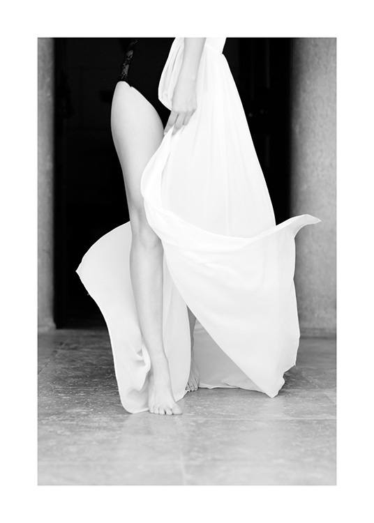 – Black and white photograph of a woman wearing a long kaftan in white, showing her right leg
