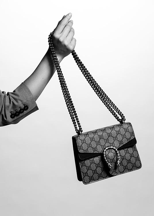 – Black and white photograph of a Gucci handbag behing held by a woman's hand