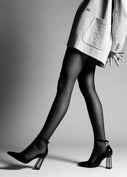 – Black and white photograph of a woman wearing a jacket, stockings and high heels