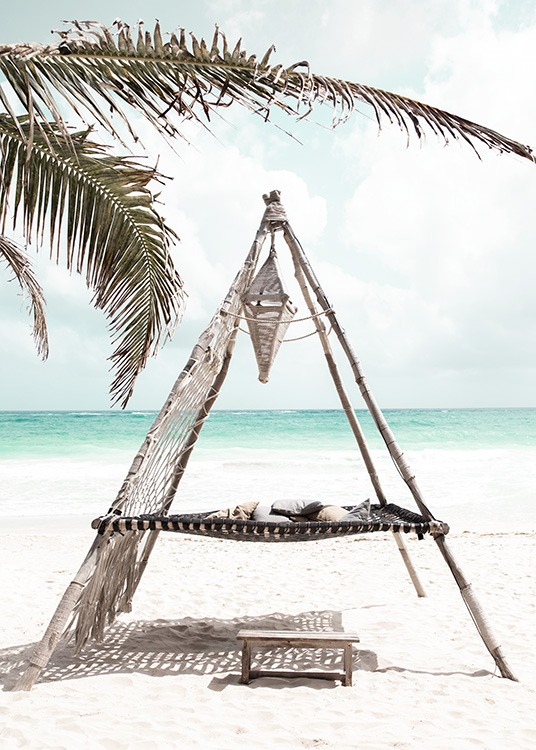 – Photograph of palm leaves in front of a hammock on a beach