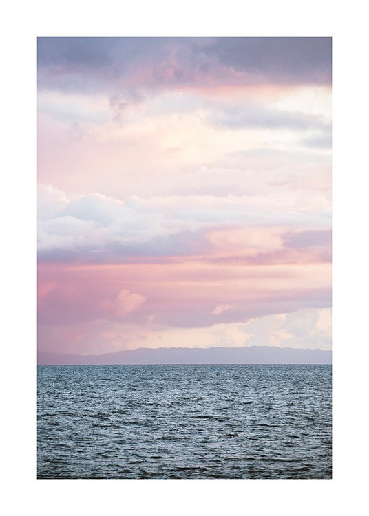 – Photograph of a sky with pastel colored clouds in pink, purple and blue above a sea