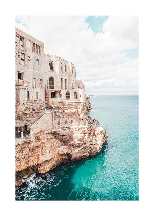 – Photograph of a cliff next to the ocean with a building on the cliff