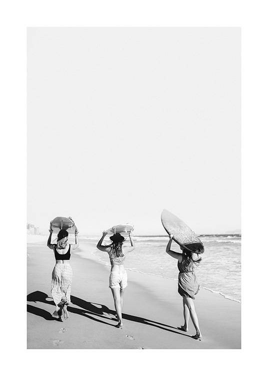 – Black and white photograph of three girls holding surfboards above their heads on the beach