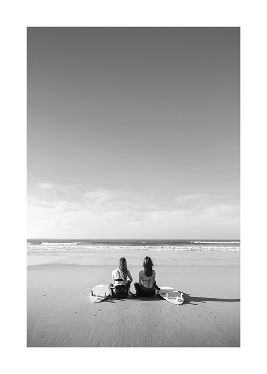– Black and white photograph of two girls sitting next to each other on the beach with their surfboards