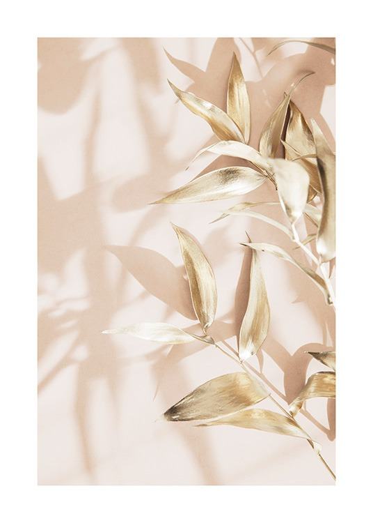 – Photograph of small leaves in gold against a light pink background