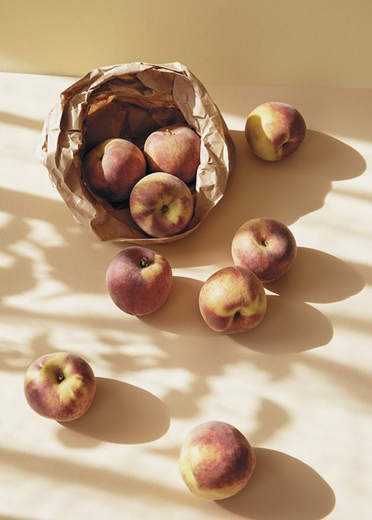 – Photograph of a brown bag with peaches in it and peaches scattered across a yellow background