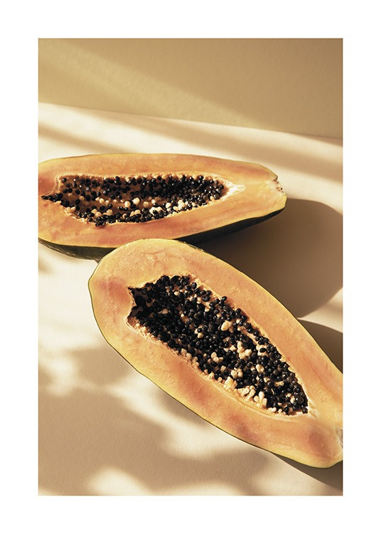 – Photograph of a papaya split in half with a yellow background