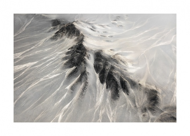 – Photograph of a mountain range from above, with light grey sides and black tops
