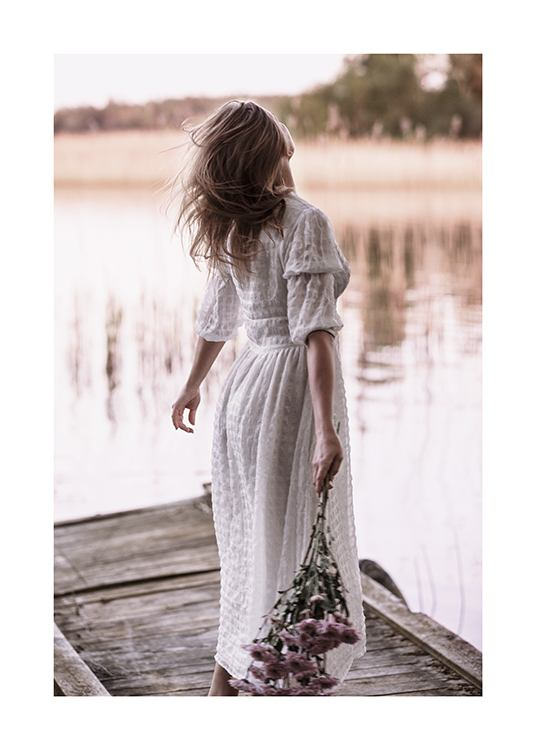 – Photograph of a woman standing on a small pier, wearing a white dress and holding a bouquet of flowers
