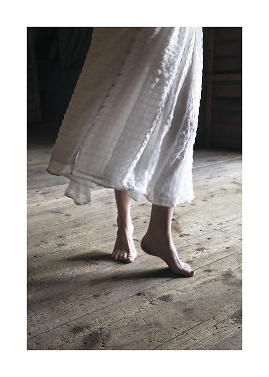 – Photograph of a woman dancing on a wooden floor, barefoot and in a white dress