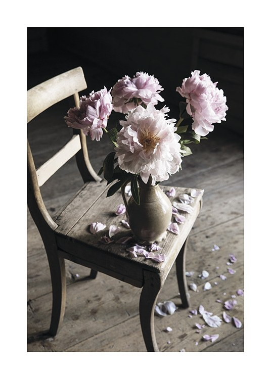 – Photograph of pink flowers in a vase on a chair, with scattered petals on the chair and floor