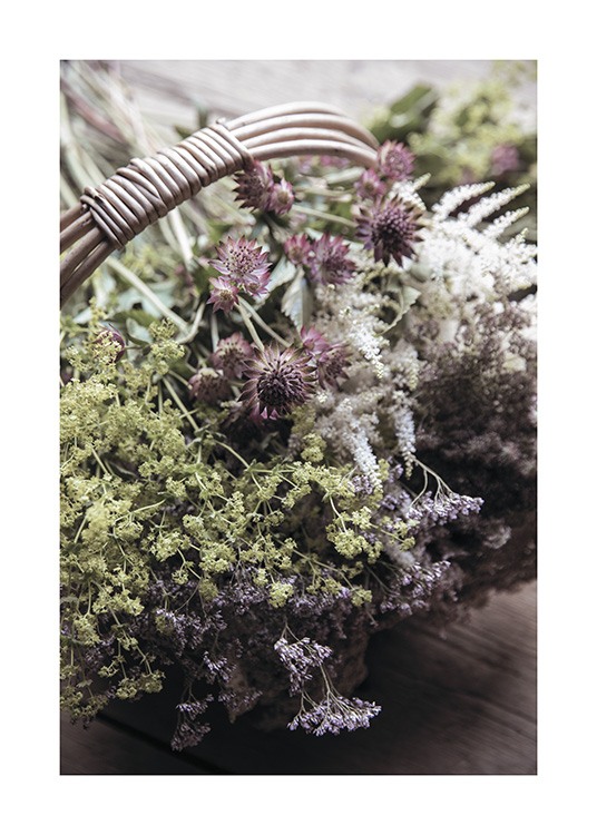 – Photograph of a bunch of wild flowers in green, white and purple in a rattan basket