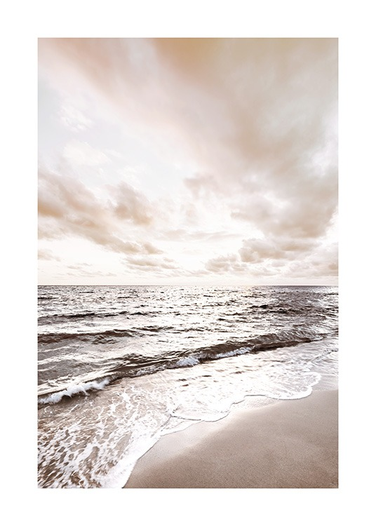 – Photograph of a calm ocean with a beach in the foreground and clouds in the background
