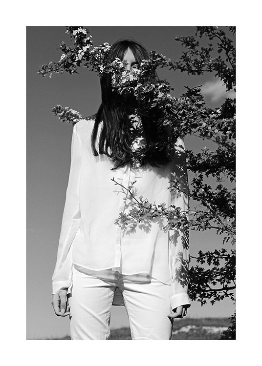– Black and white photograph of a woman in white clothes, with a tree branch in front of her