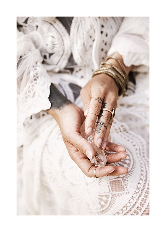 – Photograph of hands holding a crystal, with gold jewellery and a white lace dress in the background