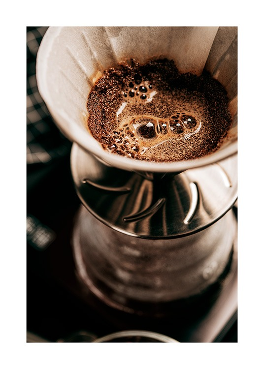 – Photograph with close up of a coffee filter filled with coffee grounds
