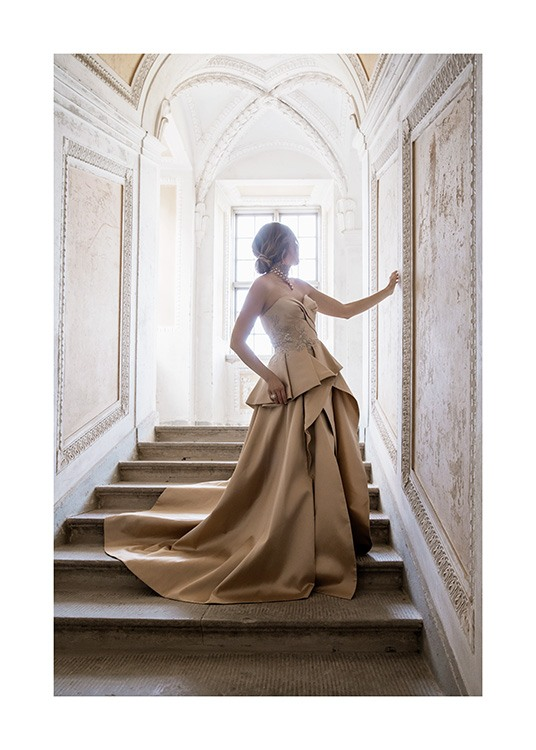 – Photograph of a woman in a gold and beige dress, standing in a staircase in a baroque style