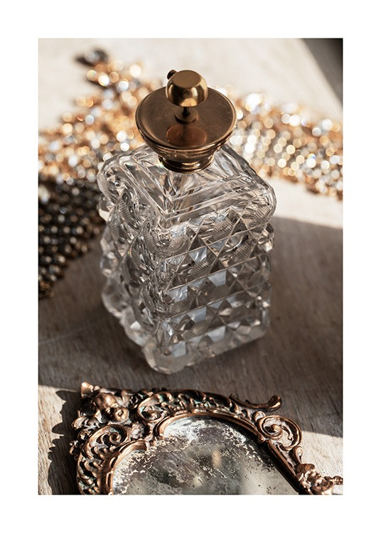 – Photograph of a retro bottle in glass with a gold lid, and a vintage mirror in front of it