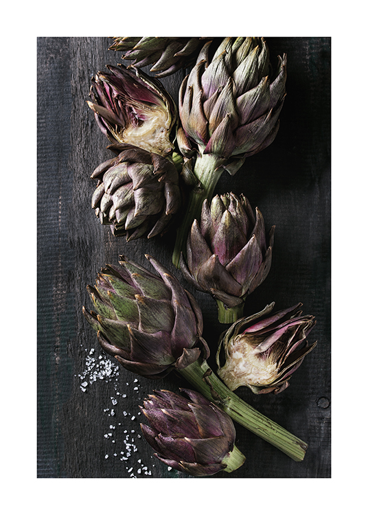 – Photograph of artichokes laying on a black, wooden table with some salt