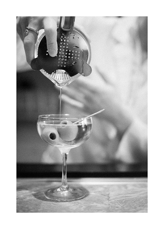 – Black and white photograph of a martini being poured from a drink shaker, with olives in the glass