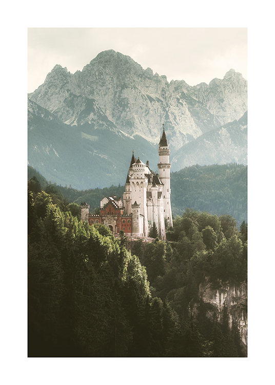 – Photograph of a castle in white surrounded by a large forest and mountains in the background