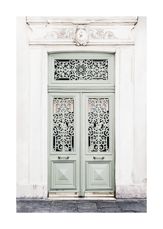 – Photograph of an antique building with a green door with carved details in the openings