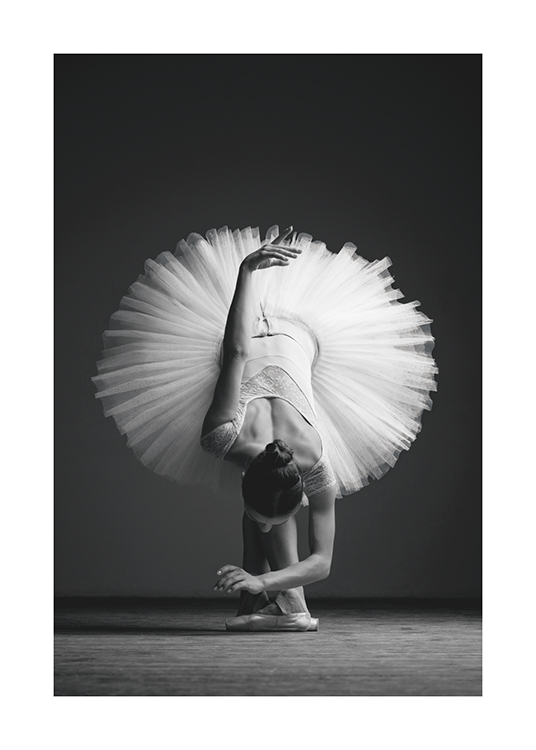 – Black and white photograph of a ballerina bending over forward in a tulle skirt