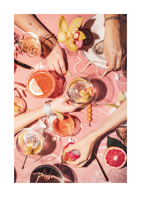 – A pastel-toned photograph of a table with cocktails, flowers, fruit and pearls