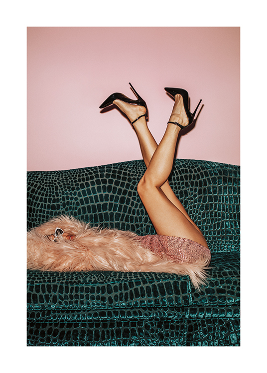 – A photograph of a woman lying on a green crocodile print sofa in a pink faux-fur coat