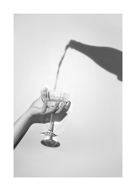 – Grey photograph of a shadow of a champagne bottle and a hand holding a champagne glass