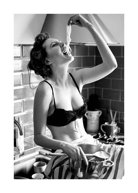 – Black and white photograph of a woman sitting in a kitchen eating pasta