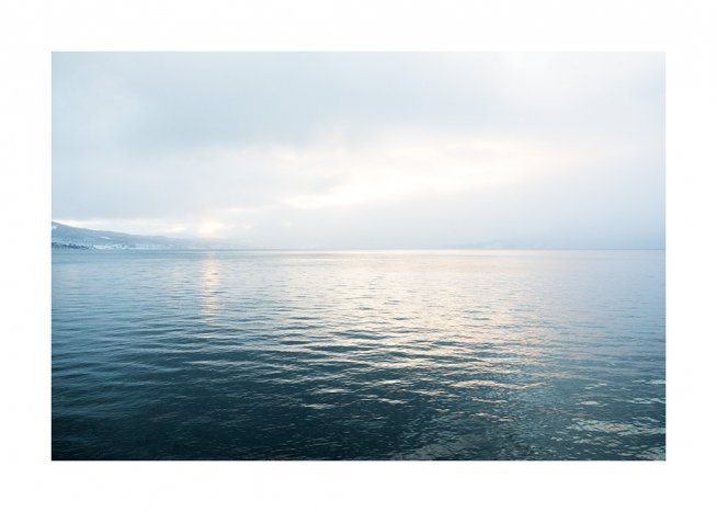 - Photograph of an ocean in sunlight with still water and mountains in the background
