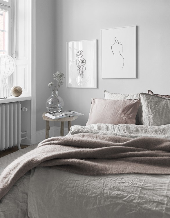 Romantic style bedroom with pale pink tones and minimalist posters